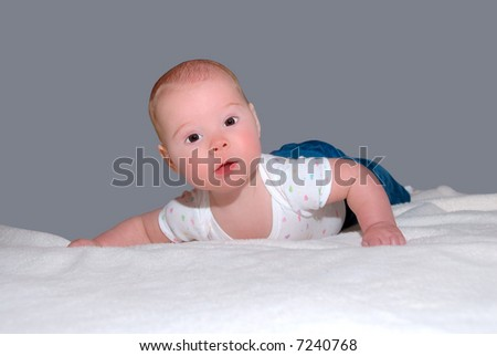Brown Eyed Baby - A brown eyed baby with a sweet expression at 4 months old lying on his stomach on a blanket.  Learning to hold her head up.