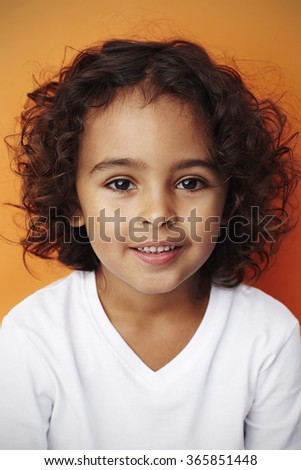 Brown eyed boy portrait on orange background