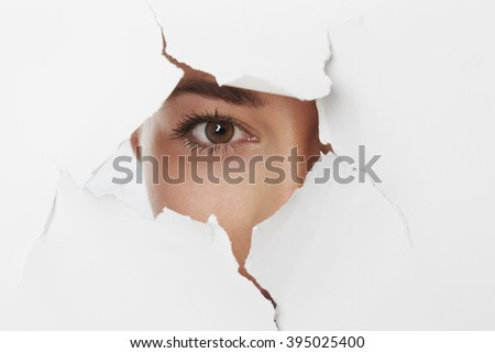 Brown eyed girl looking through ripped paper
