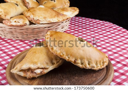 Brown Filled pastry with Pizza Soauce on round wood plate - stock photo