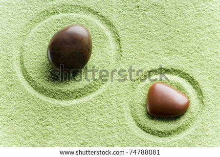 brown flat stones in blance in a circle on green sand