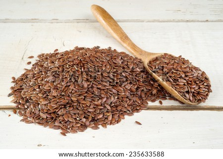 brown flax seed on wooden table - stock photo