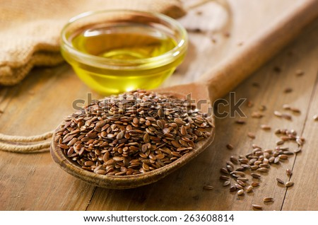 Brown flax seeds on a spoon and flaxseed oil. - stock photo