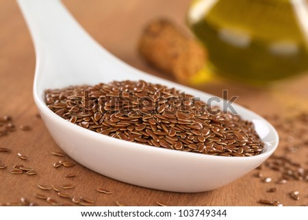 Brown flax seeds on ceramic spoon with linseed oil in the back (Selective Focus, Focus on third into the flax seeds on the spoon) - stock photo