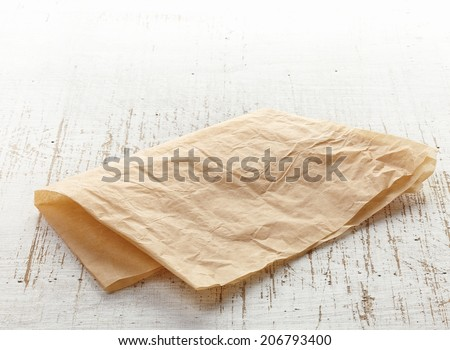 brown folded wrapping paper on wooden table - stock photo
