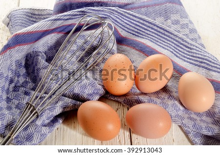 brown free range eggs and a whisk on kitchen towel