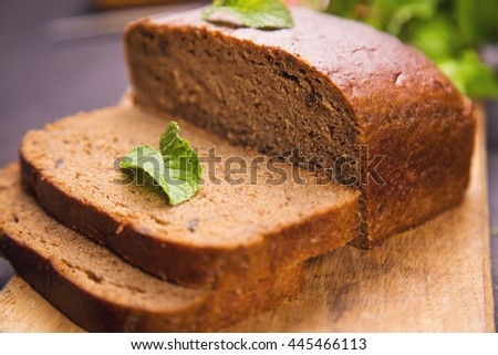 brown fresh bread with green mint and knife on wooden background