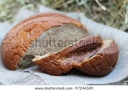 Brown fresh sliced bread and flax textile on hay