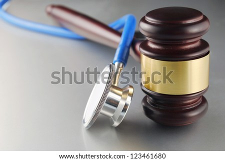 brown gavel and a medical stethoscope on gray background - stock photo