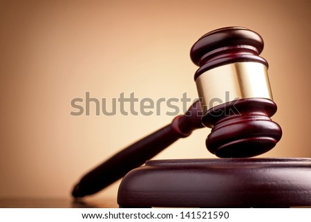 brown gavel on the table on a brown background - stock photo