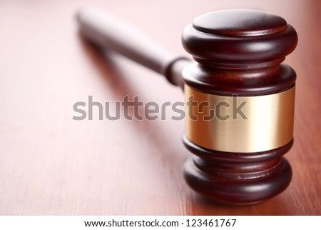 brown gavel with a brass band on a brown background