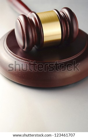 brown gavel with a brass band on a gray background