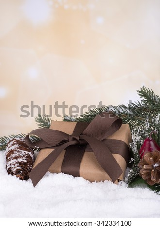 Brown gift box on snow with decorations and holiday background - stock photo
