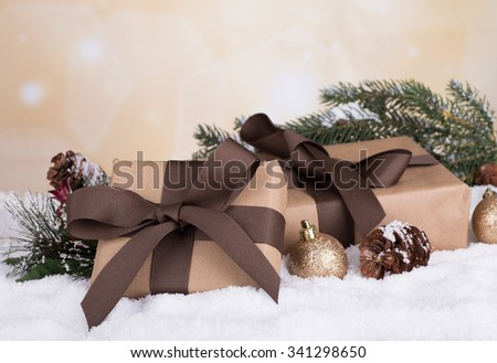 Brown gift boxes with Christmas ornaments on snow with colorful holiday background