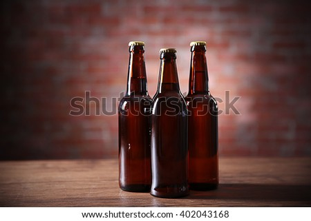Brown glass bottles of beer on brick wall background - stock photo