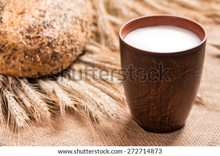 Brown glass cup of milk, bread, sackcloth are on burlap. Glass cup of milk standing on sackcloth and in the background a loaf of bread and spikelets of wheat. Horizontal frame. Close-up.