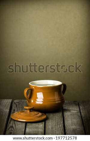 Brown glazed ceramic crock or lidded bowl with two side handles on a rustic wooden kitchen counter against a plain grunge brown wall with plenty of copyspace and a vignette - stock photo