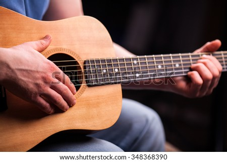 Brown guitar in hands in the guy playing it - stock photo