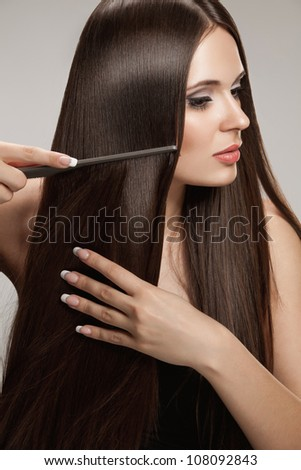 Brown Hair. Beautiful Woman combs her Healthy Long Hairr. High quality image.