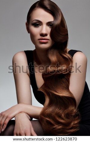 Brown Hair. Portrait of Beautiful Woman with Long Wavy Hair. Good quality retouching.