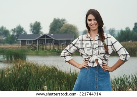 brown haired countryside lady posing against ranch house and pond. She stands near tall grass and reed against rural scape. She wears jeans dress. House has one floor. It is made of wood and is brown - stock photo