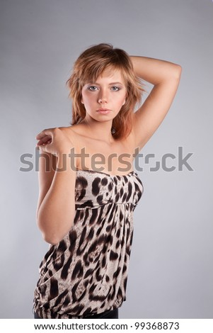 brown-haired girl dressed in a tiger, leopard fabric poses in the studio