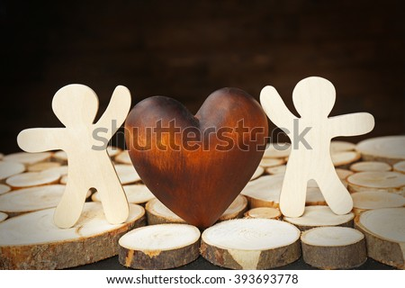 Brown heart with two figures on wood logs
