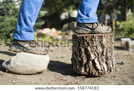 Brown hiking shoes on a stump in the forest