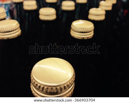 Brown ice beer bottles golden caps assorted in lines