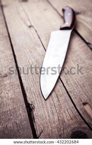 Brown knife on an old kitchen. Cooking, cutting, cooking. On wooden background