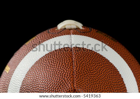Brown leather american football on black background