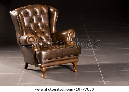 Brown leather armchair on a black background - stock photo