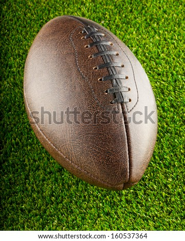 Brown leather football over a background of green grass - stock photo