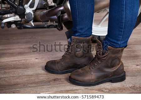 Brown leather half-boots for motorcycling, female legs in jeans are near motorbike, close up view