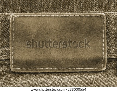 brown  leather label on brown  jeans background
