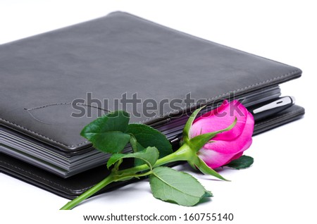brown leather notebook and rose over a white background