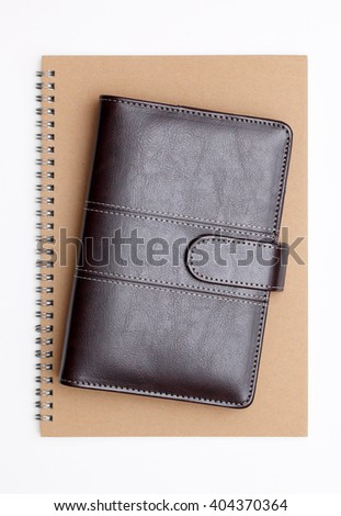 brown leather notebook and spiral notebook on white background