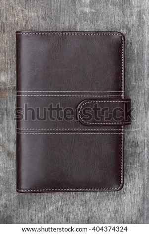brown leather notebook on grunge wooden table background  - stock photo