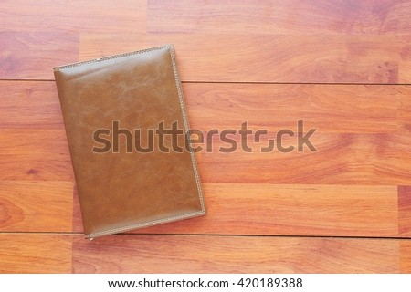 Brown leather notebook  on wood table. - stock photo