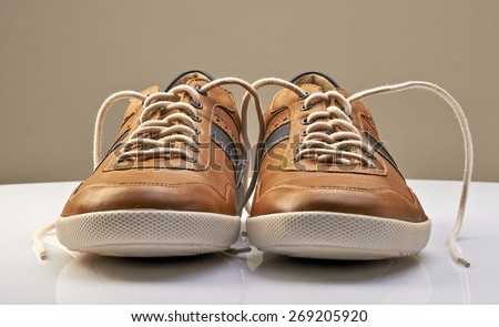 Brown Leather Shoe with white shoelaces open on a white table - stock photo