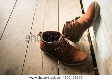 Brown leather shoes on wooden floor.