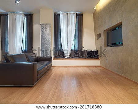 Brown leather sofa in front of television in modern living room with wooden floor - stock photo