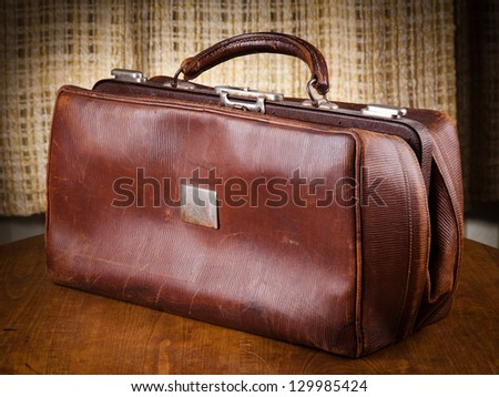 Brown leather suitcase over warm wooden table - stock photo