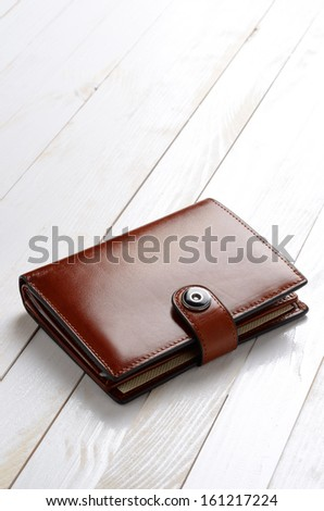 Brown leather wallet on white wooden table - stock photo