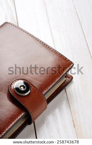 Brown leather wallet on white wooden table. Closeup shot - stock photo