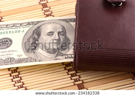 brown leather wallet with dollars - stock photo