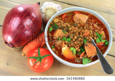 Brown lentil Soup and ingredients carrots, bulbs red onion and Garlic, Tomato, smocked sausage, seasonings parsley, dill in gray porcelain bowl over gray wooden table  - stock photo
