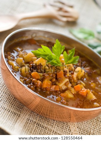 Brown lentil soup in bowl with vegetable, selective focus - stock photo