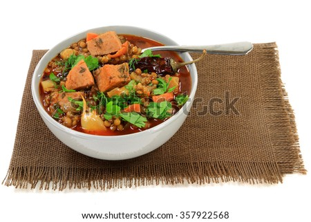 Brown lentil Soup, ingredients carrots, onion, celery, smocked sausage, dry cayenne (Chili) pepper, seasonings garlic, parsley, dill in gray porcelain bowl sprayed with fresh chopped parsley, dill  - stock photo