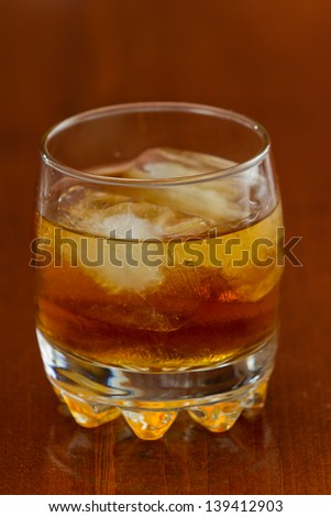 brown liquor served on the rocks on a busy bar with a shallow depth of field